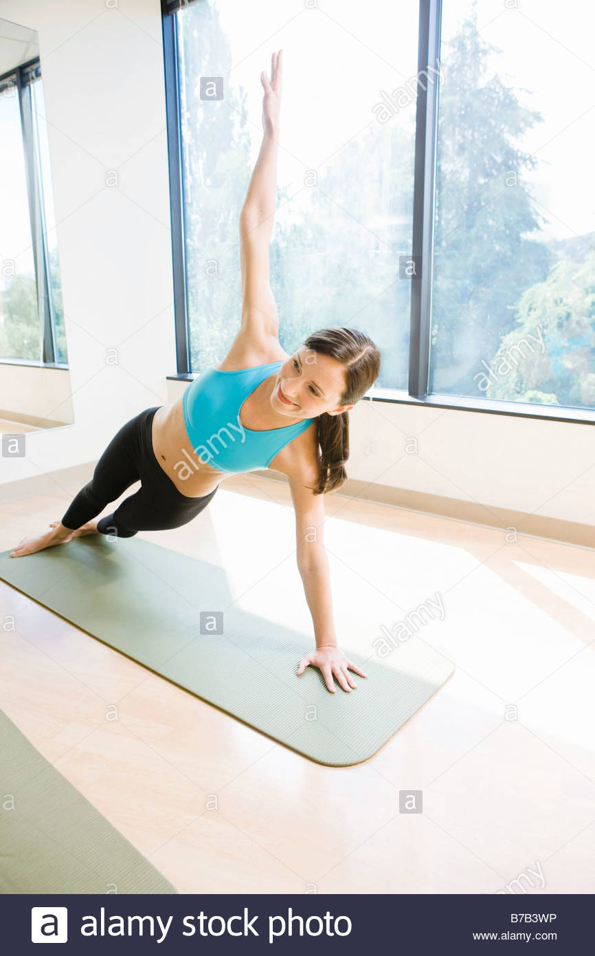 Portrait of Native American woman doing side plank exercise - Stock Image