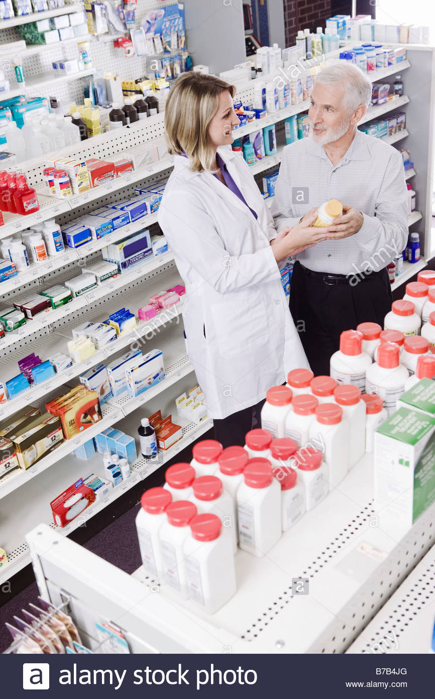 Pharmacist helping customer with over-the-counter products - Stock Image