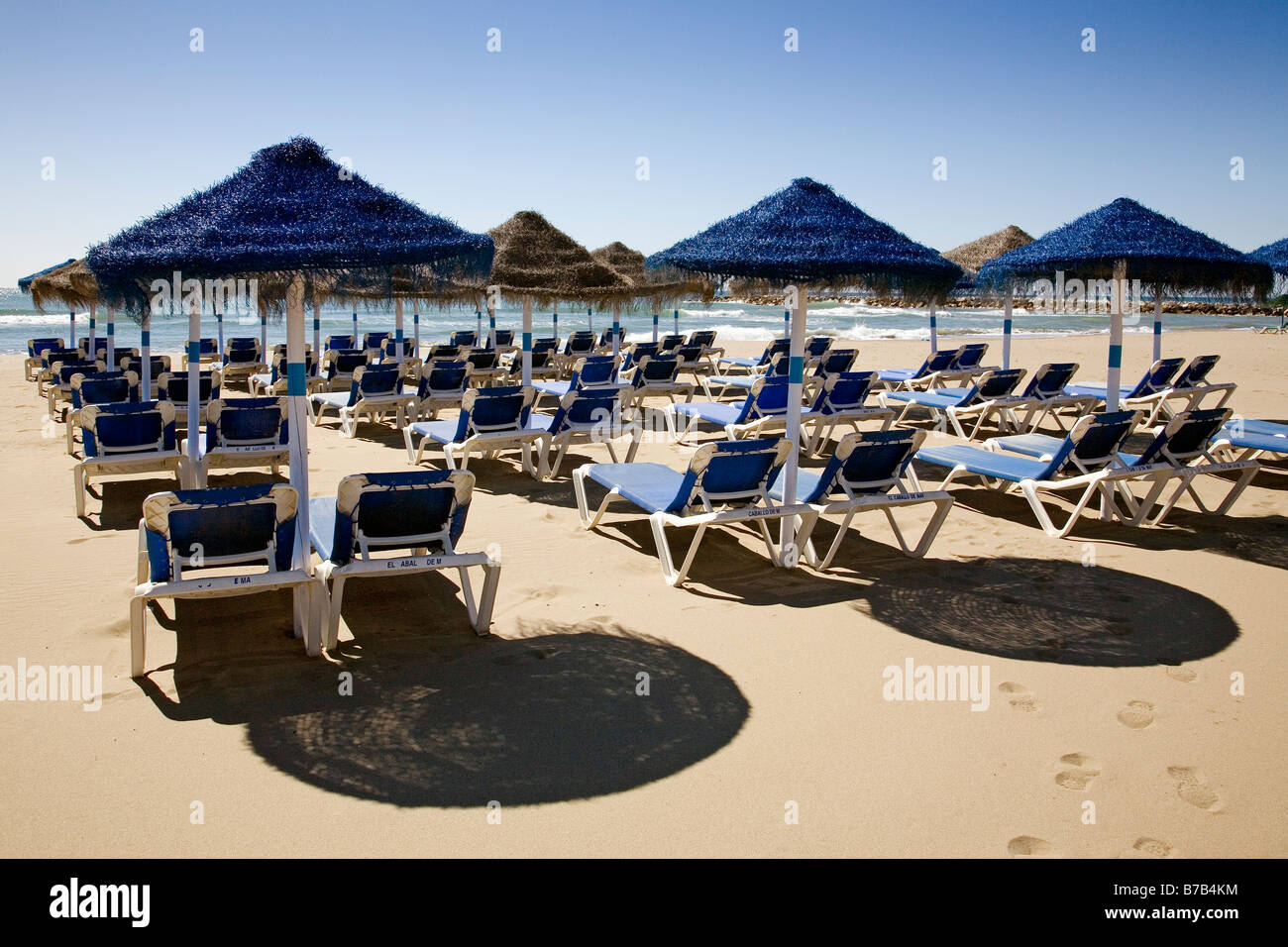 Umbrellas and hammocks on Cabopino beach Marbella Malaga sun coast Andalusia Spain - Stock Image