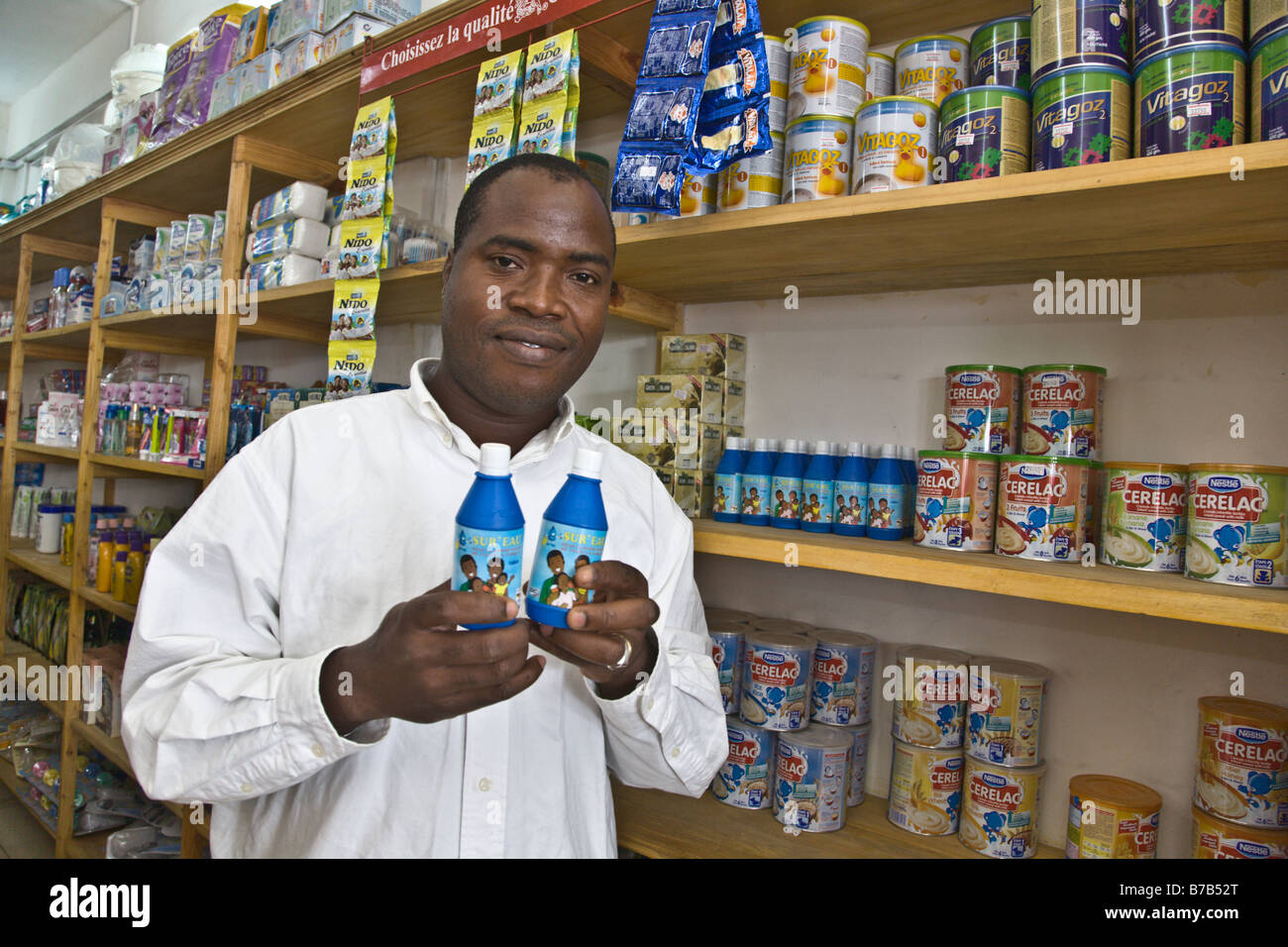 A salesman at a grocery store in Conakry, Guinea, holds up bottles of Sur'Eau, a chlorine product. - Stock Image
