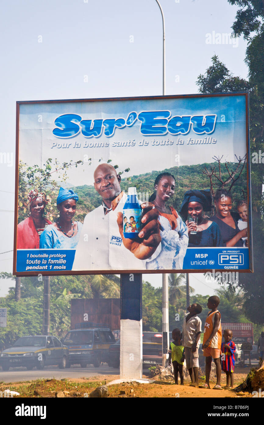 Children look up at a billboard advertising Sur'Eau on a busy street through Guinea's capital city of Conakry. - Stock Image