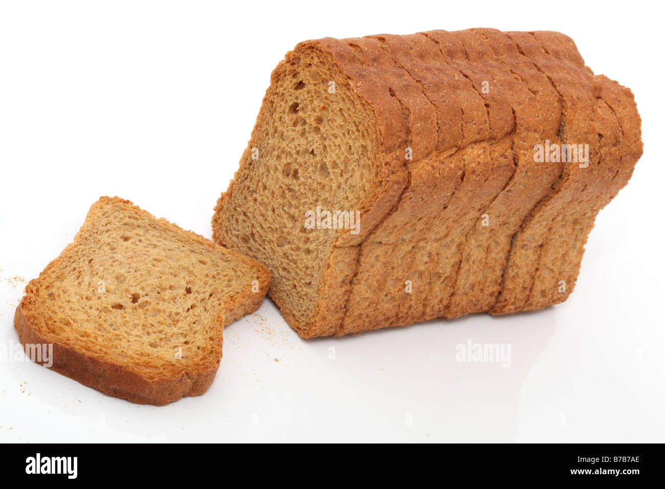 dry toasted bread loaf in slices isolated on white background - Stock Image