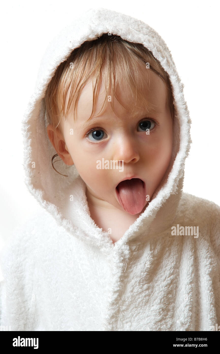 toddler in white bathroom pulling tounge out - Stock Image