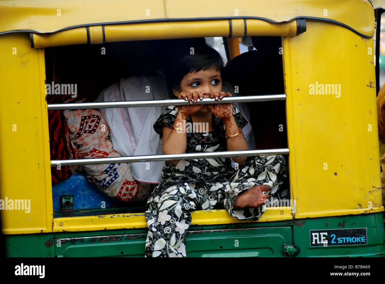 Girl with henna patterns on her hands leaning out of auto-rickshaw, Ahmedabad, India. - Stock Image