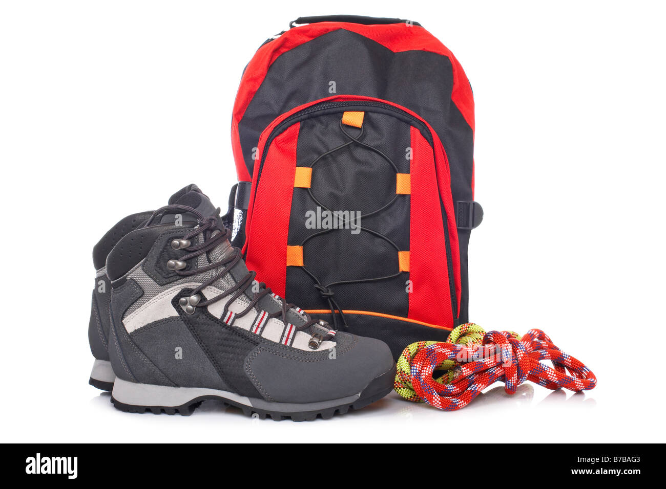 Hiking boots two rope and backpack reflected on white background - Stock Image