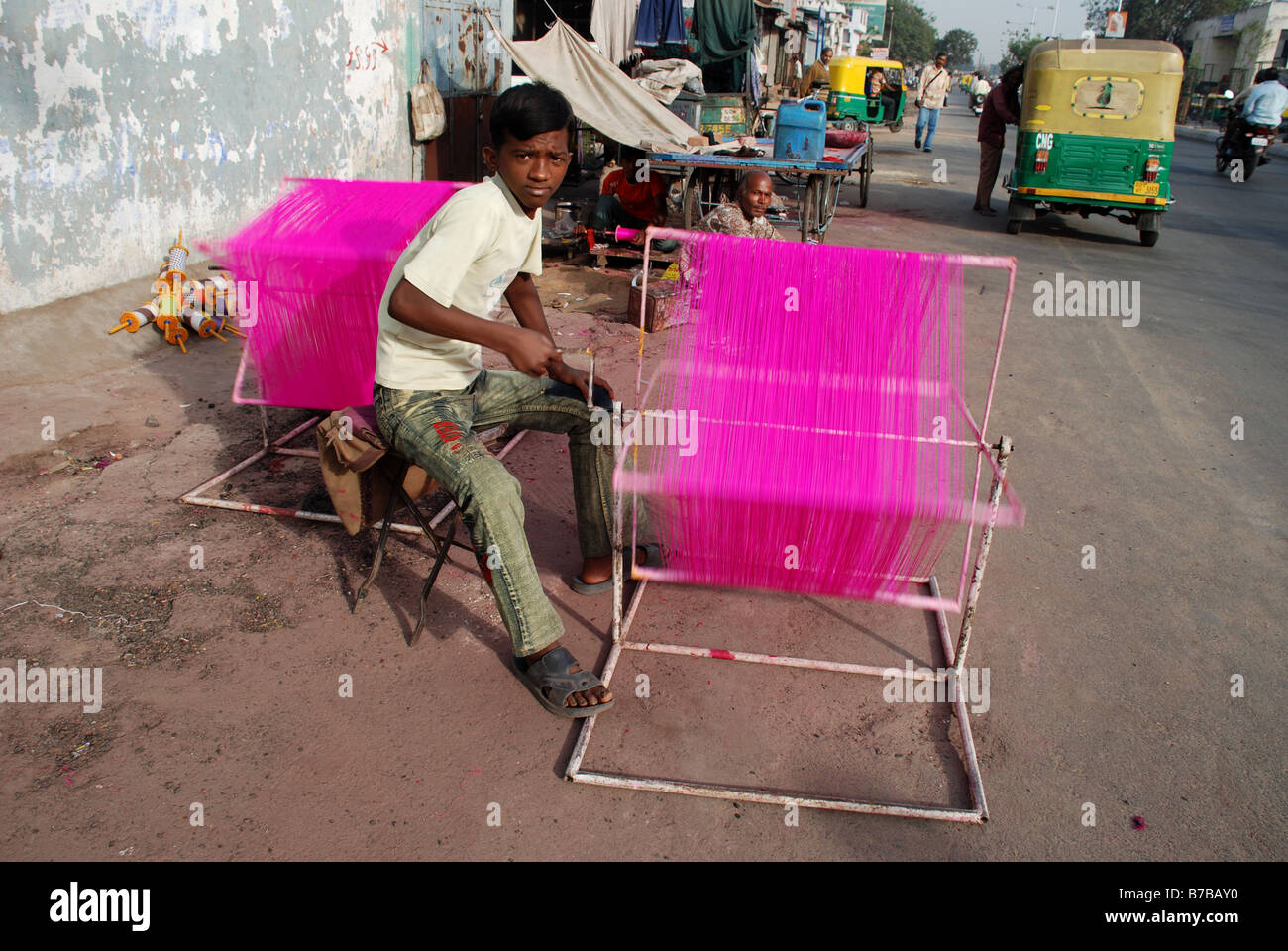 Boy dyeing thread in the street in preparation for the Kite Festival, Ahmedabad, India. - Stock Image