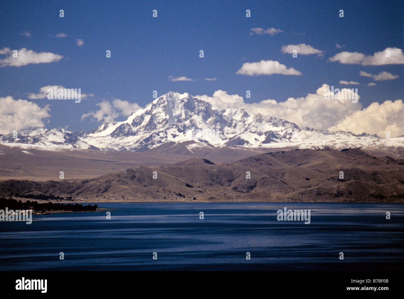 Bolivian Andes peak Mount Nevado Illampu and Lake Titicaca, view from Isla del Sol - Stock Image