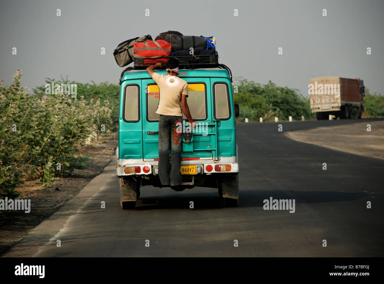 Boy holding onto the back of a vehicle in Ahmedabad, India. - Stock Image