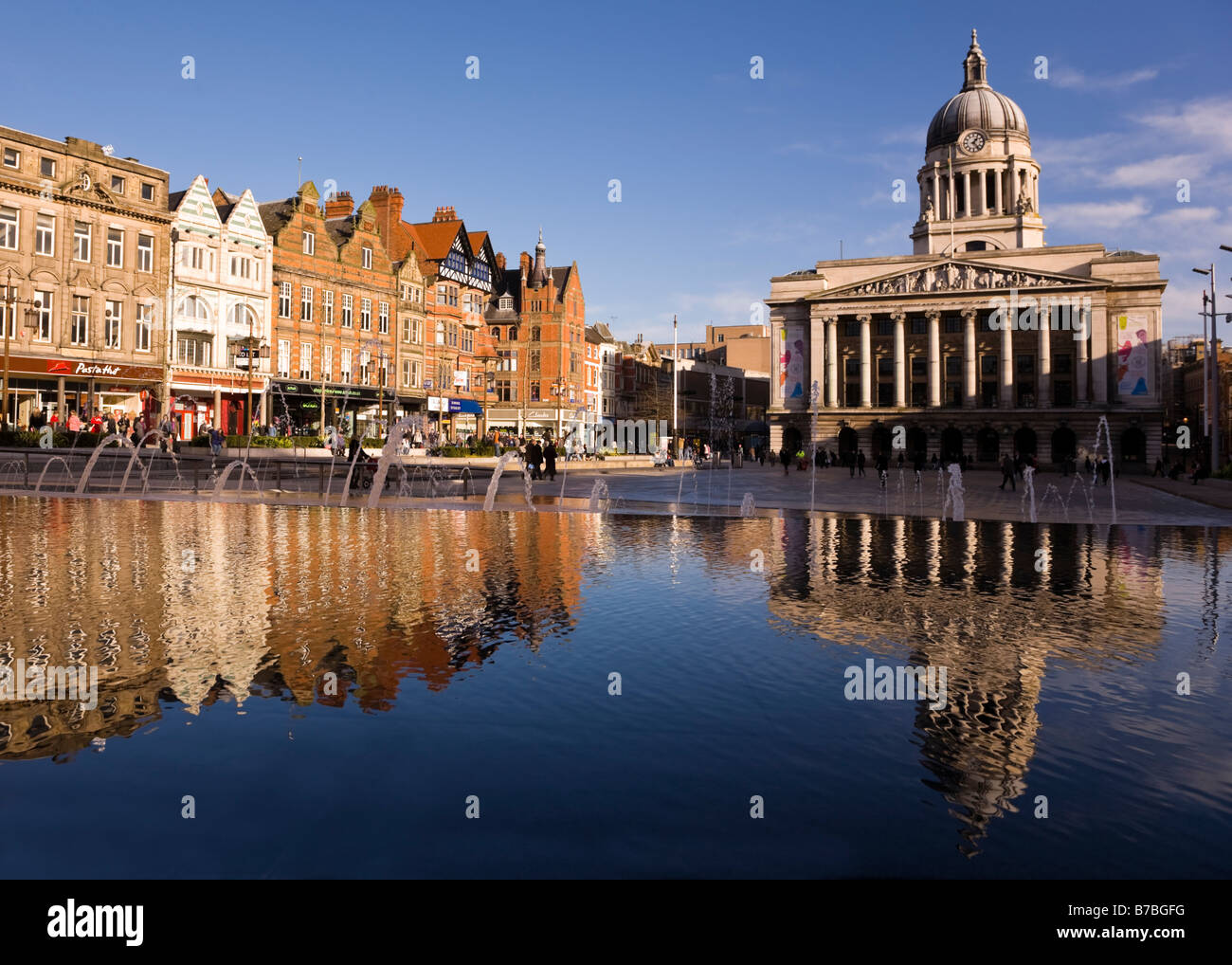 Nottingham City Hall and shops in the Market Place reflected in the waters of the fountain - Stock Image