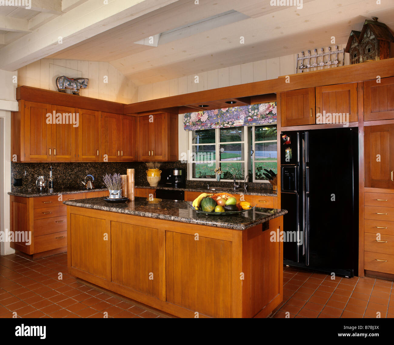 A modern KITCHEN with custom wood cabinets marble counter tops and a black refredgerator Stock Photo