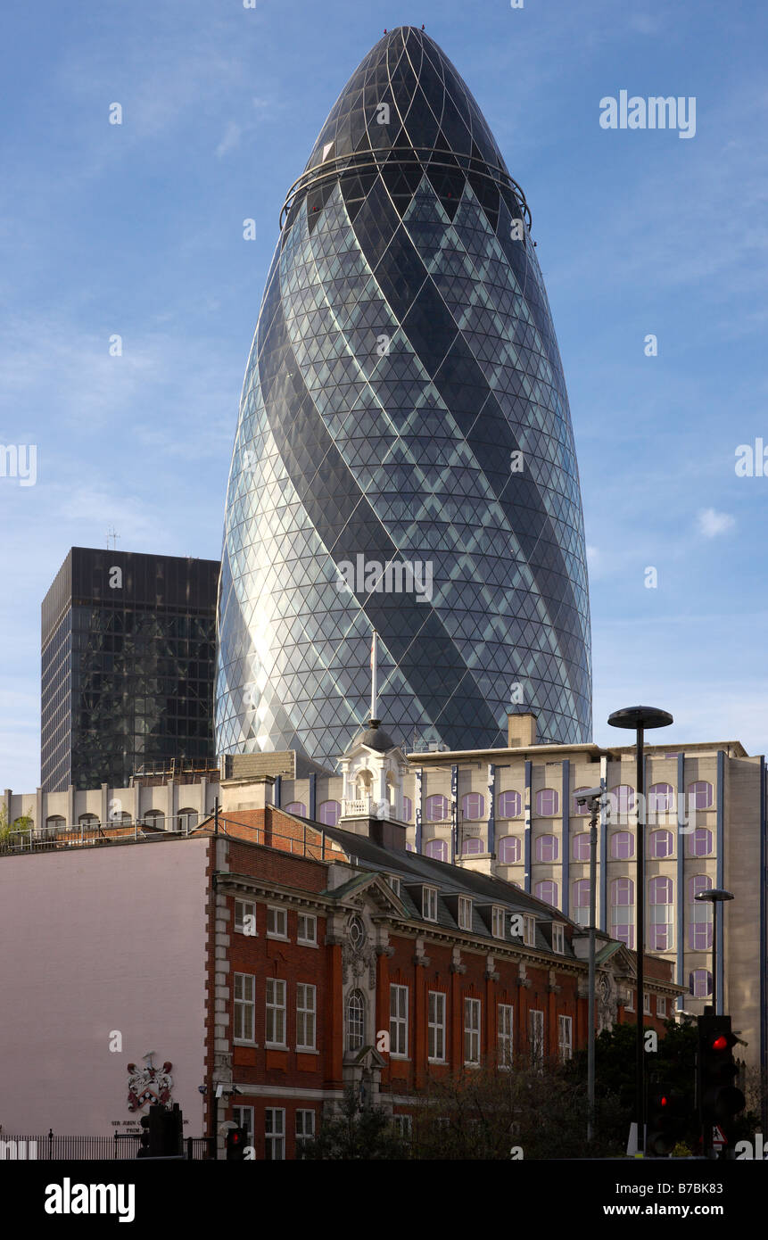 The 'Gherkin' at 30 St Mary Axe in London seen behind older buildings including the Sir John Cass foundation - Stock Image