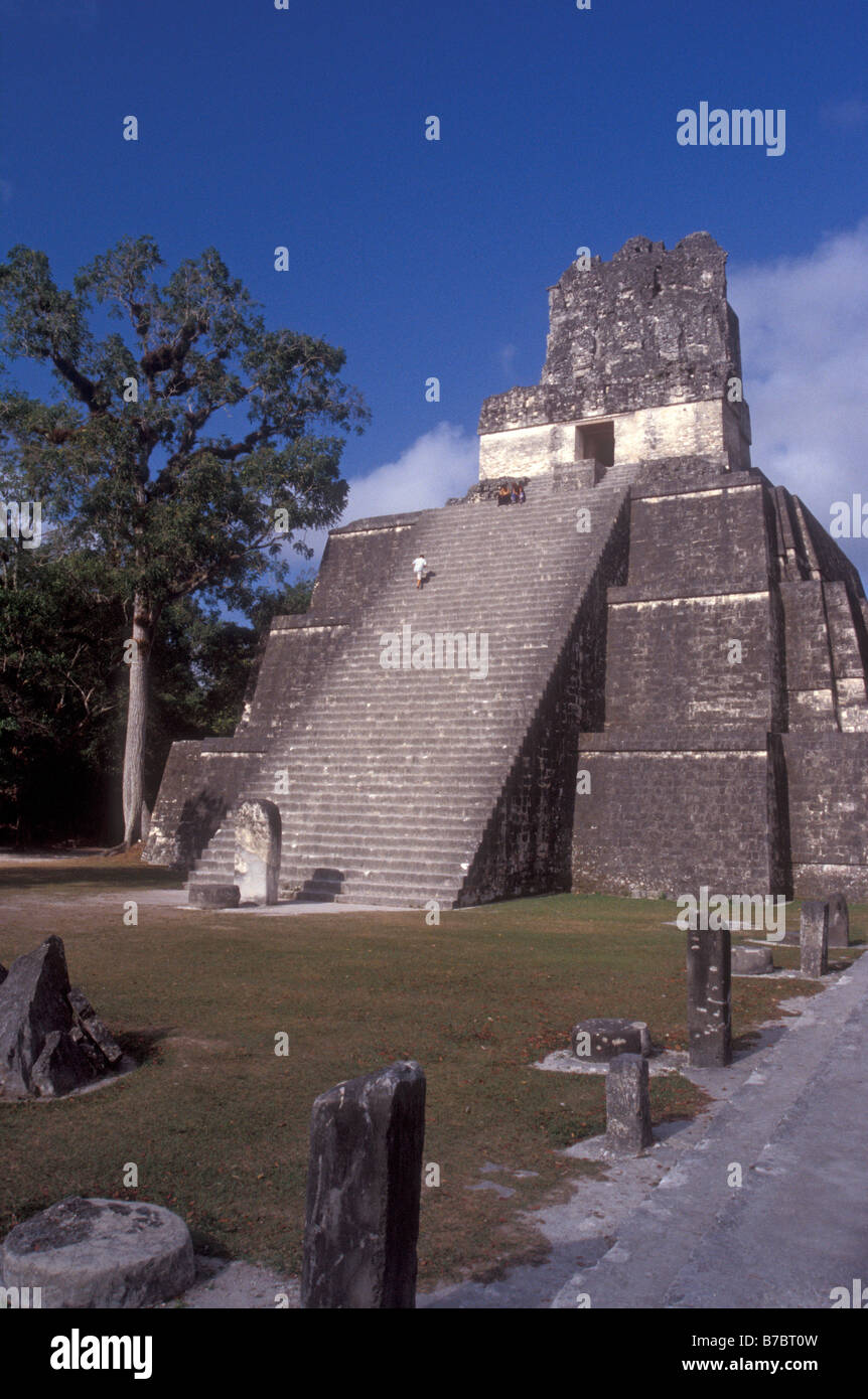 Tourist climbing Temple II or Temple of the Masks at the Mayan ruins of Tikal in Tikal National Park, El Peten, Stock Photo