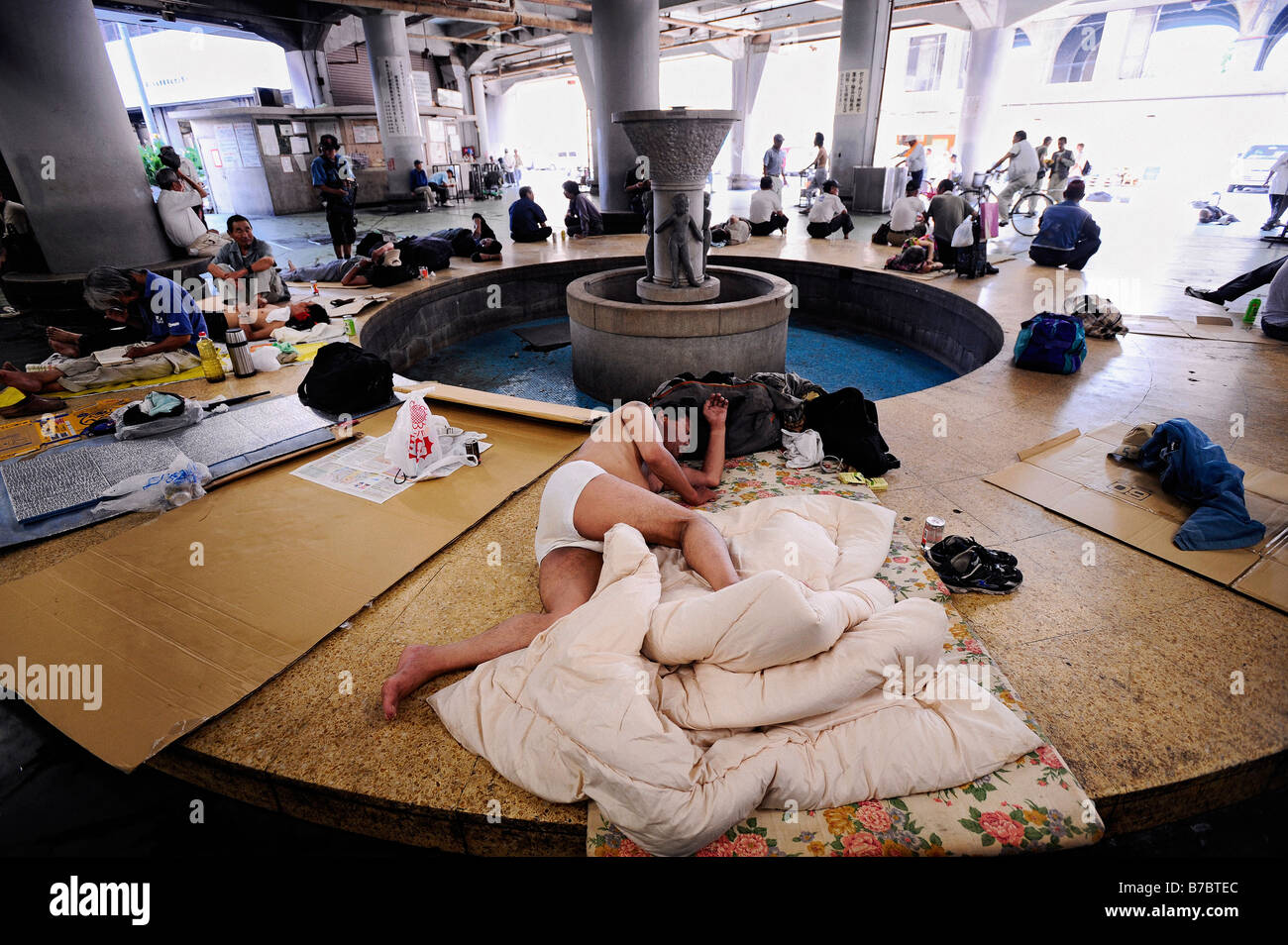 Homeless and jobless men hang around a communal area of the Nishinari Labor Welfare Center in the Kamagasaki district - Stock Image