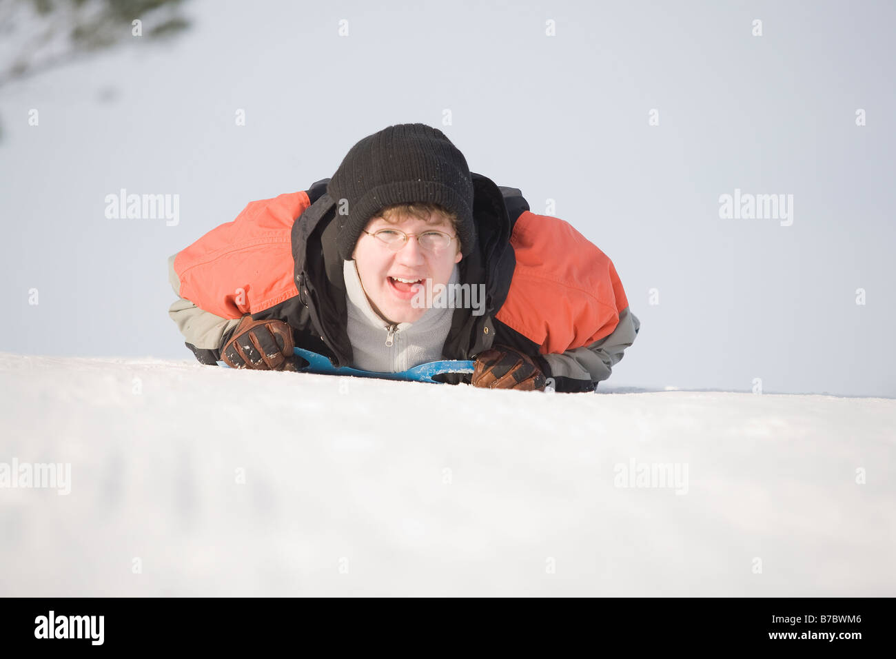15 year old slides down hill luge-style, Winnipeg, Canada - Stock Image