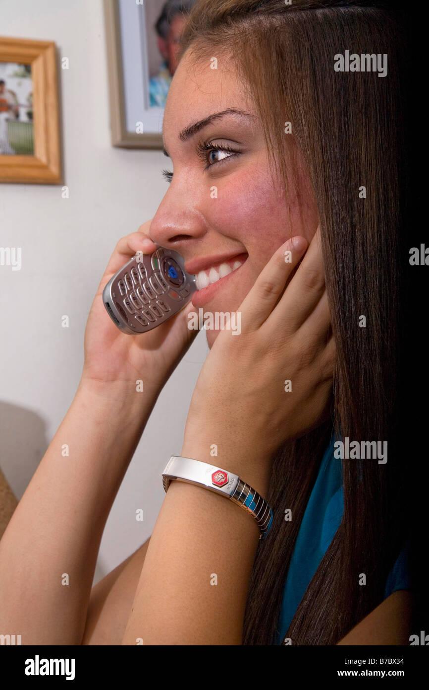 Hispanic girl woman female phone telephone communicate talk friend share listen express visit laugh smile happy - Stock Image