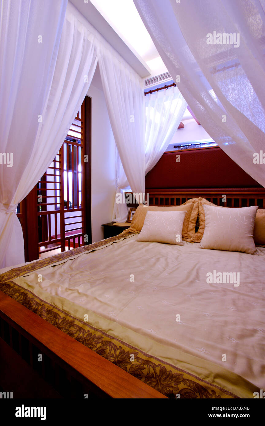 Luxurious four poster bed with white curtains tied up at the four corners - Stock Image