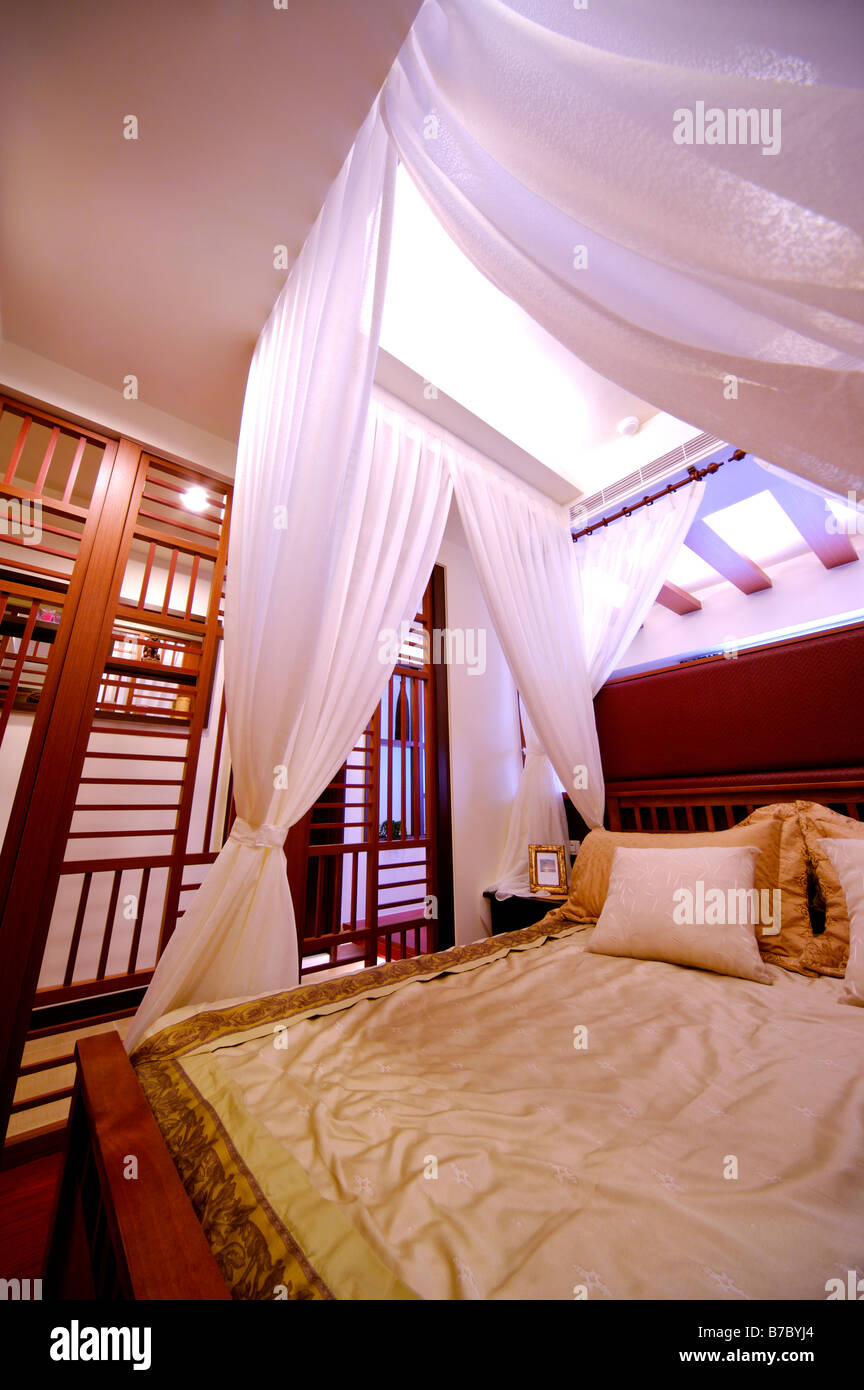 Four poster bed with white curtains Stock Photo