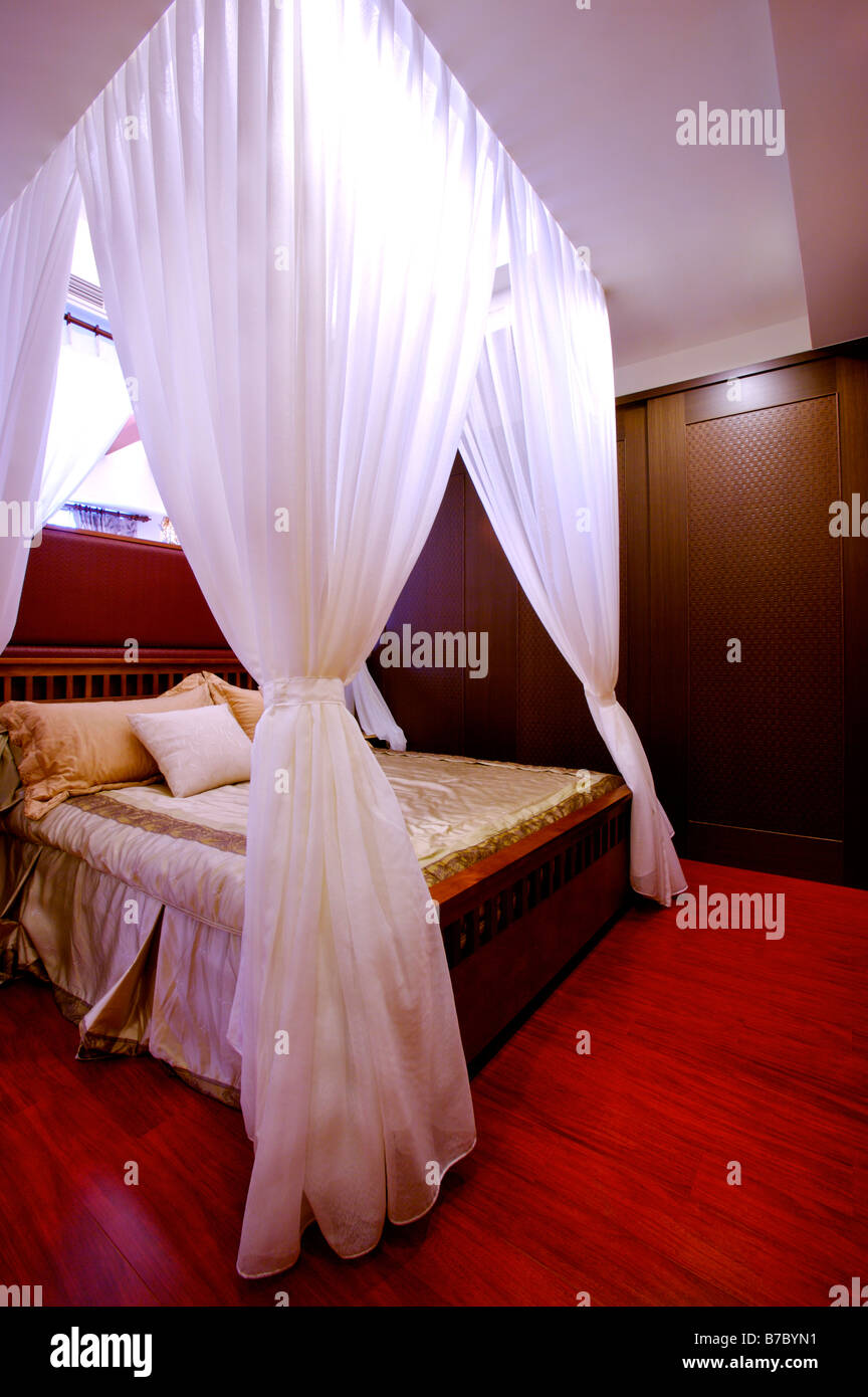 Four poster bed with white curtains tied up at the corners in the bedroom Stock Photo