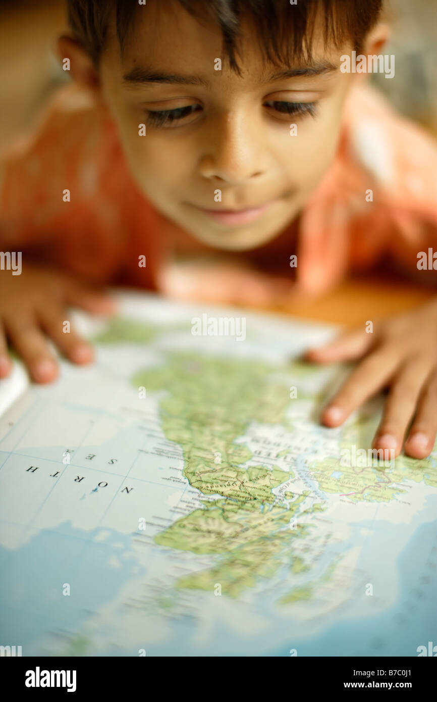 Six year old boy looks in atlas at map of UK - Stock Image