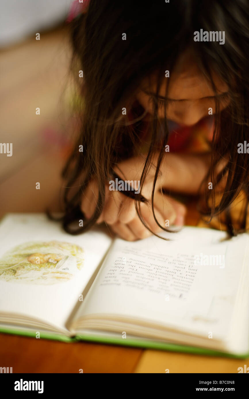 Five year old girl lies on floor reading Beatrix Potter book - Stock Image