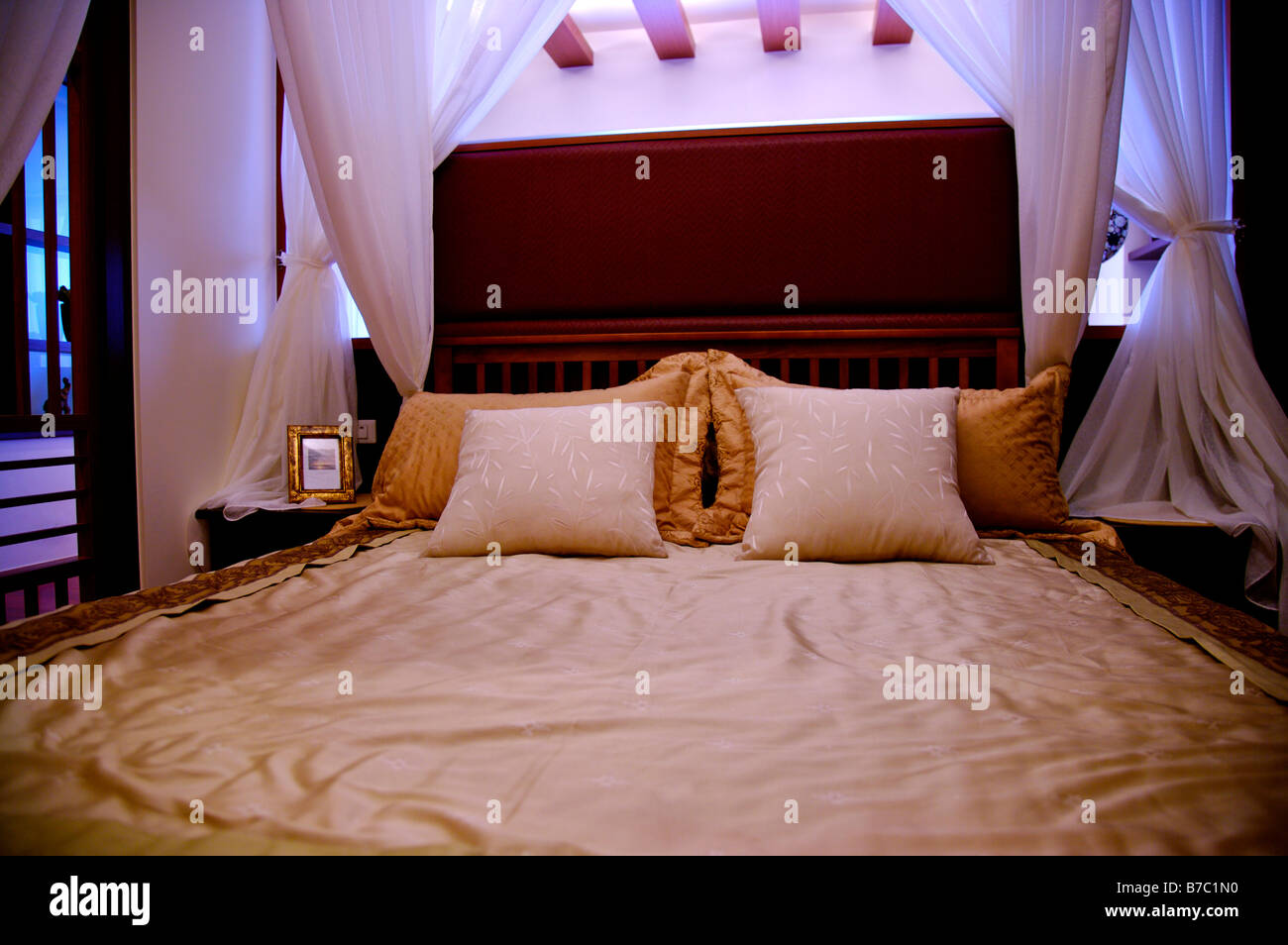 Four poster bed with white curtains and a photo frame beside the bed - Stock Image