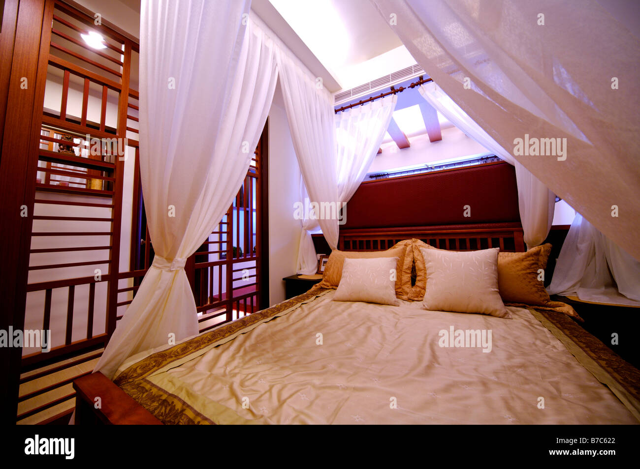 Modern four poster bed with white curtains at the four corners Stock Photo