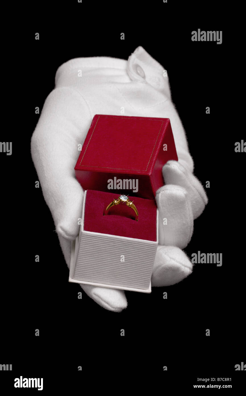 Hand wearing a white glove presenting a diamond ring in a proposal of marriage Isolated on a black background - Stock Image