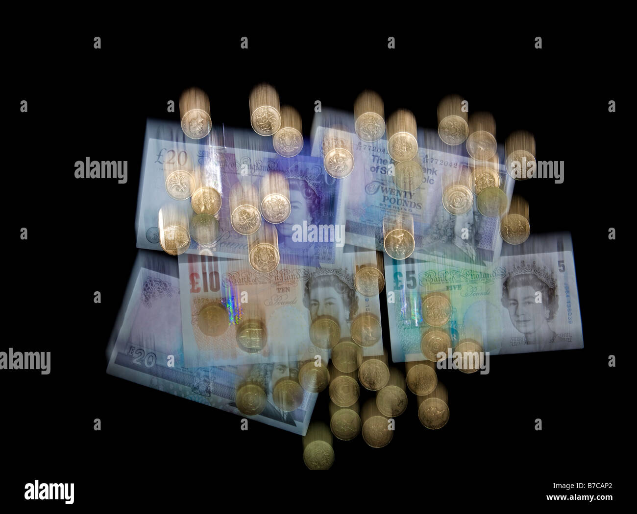 Falling blurred UK currency, banknotes and pound coins sterling to illustrate the falling pound Stock Photo