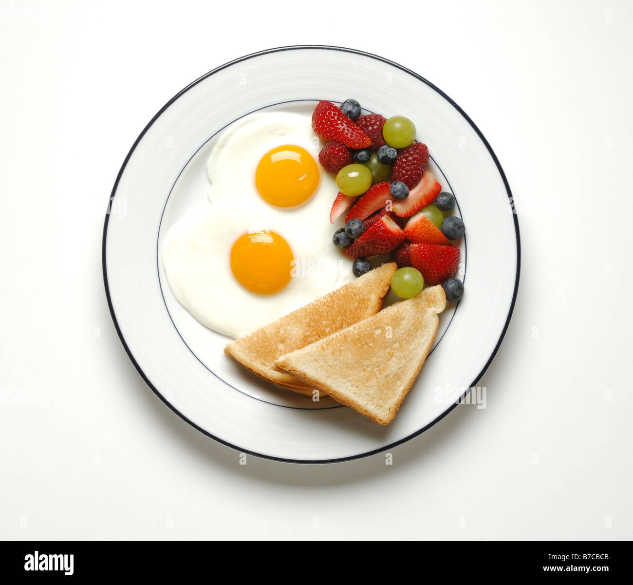 A breakfast serving of fried eggs, toast and mixed fruits - Stock Image