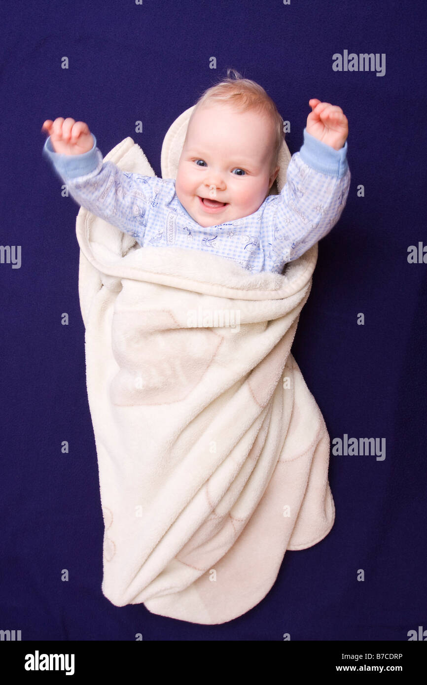 Smiling suckling baby 7 months old convoluted in cover - Stock Image