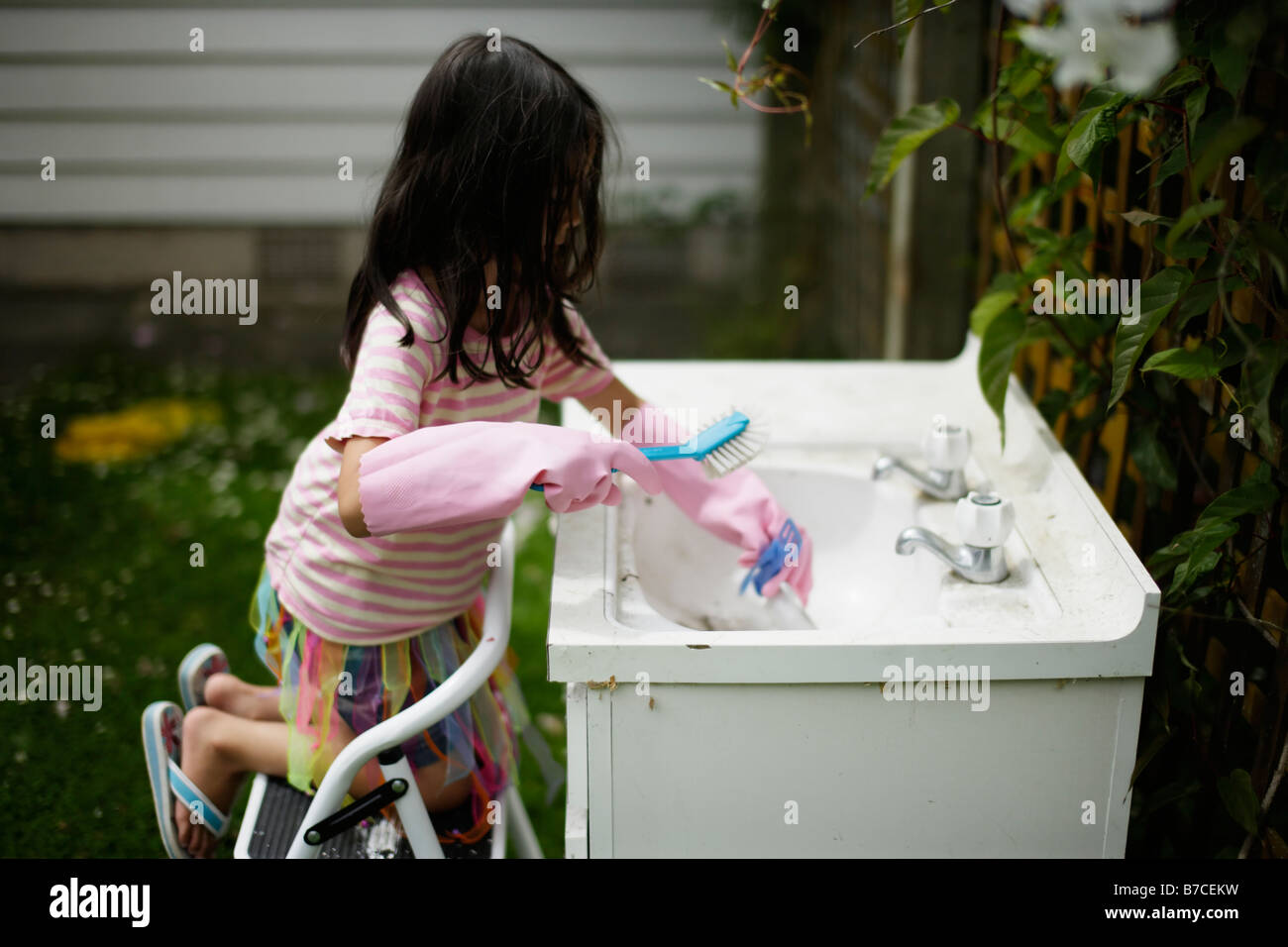 Six year old girl plays at washing up in old disused sink in garden - Stock Image
