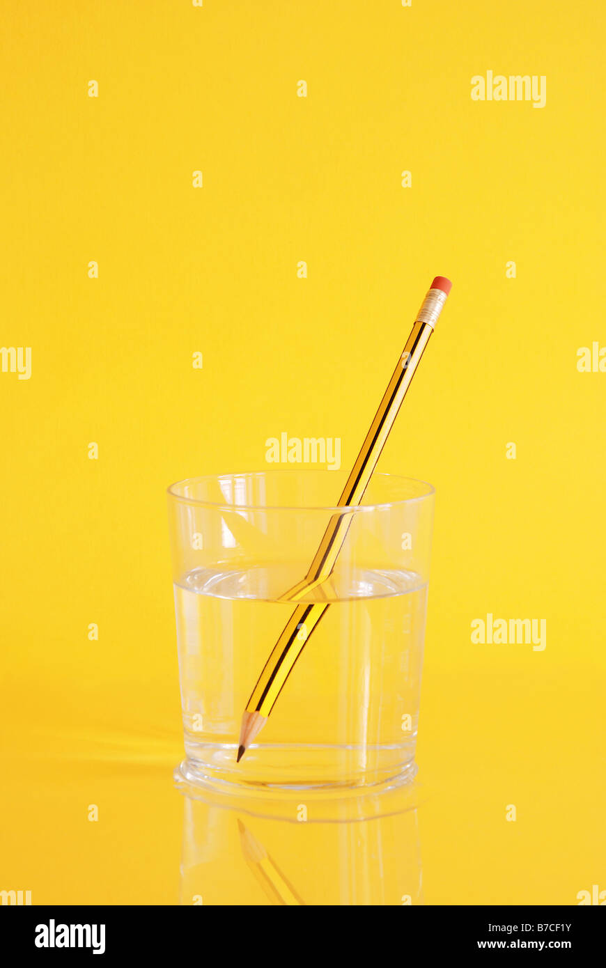 Pencil in glass of water. - Stock Image