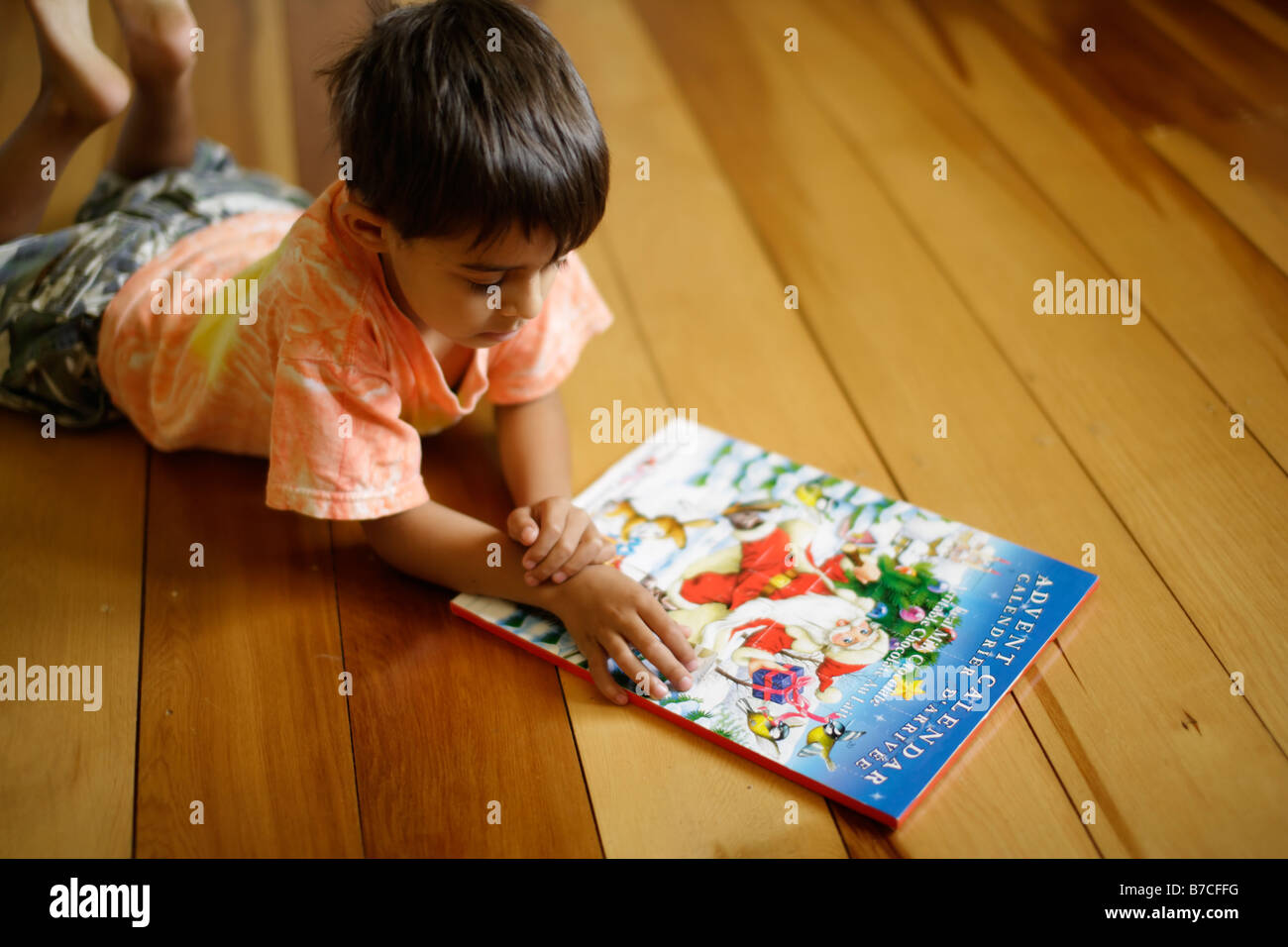 Six year old boy lies on floor and opens doors to advent calendar - Stock Image