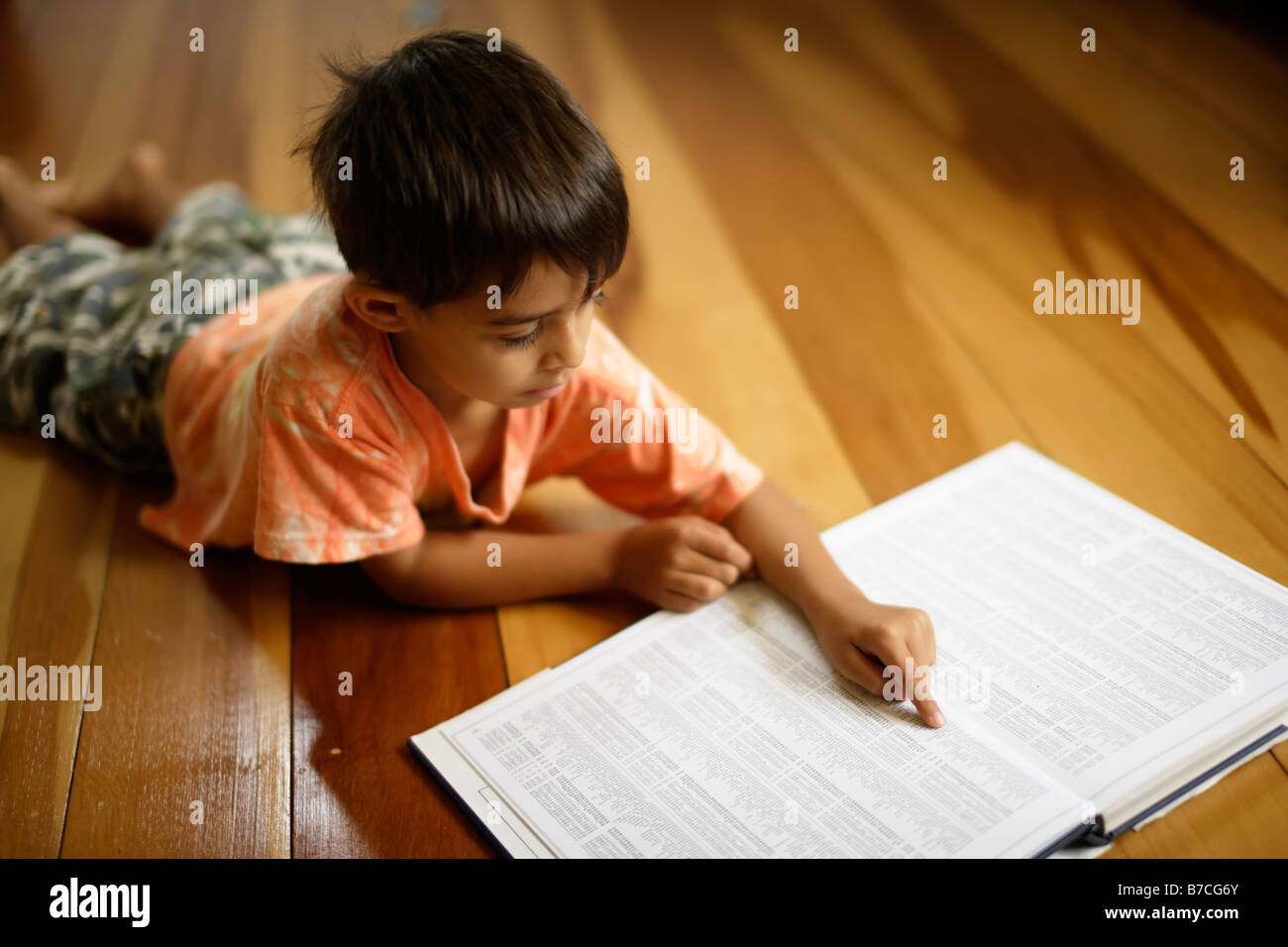 Six year old boy points to index of atlas - Stock Image