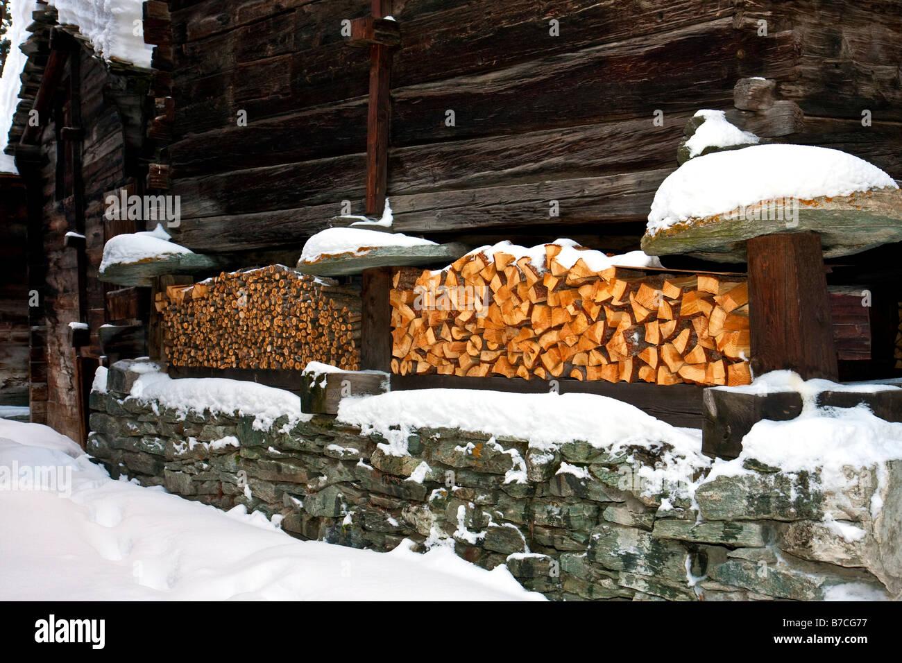 Fire wood stacked for winter in Zermatt Switzerland - Stock Image