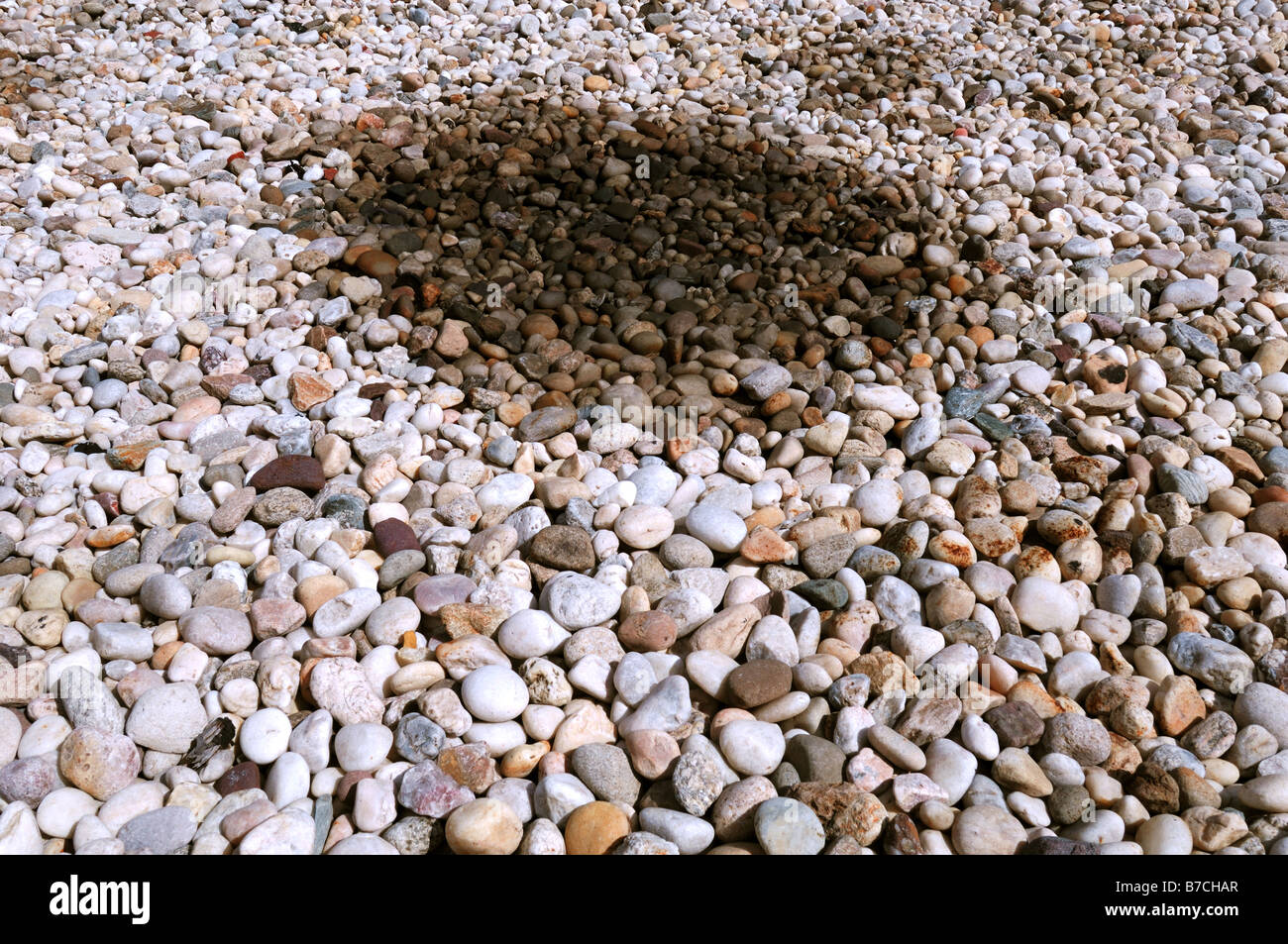 An oil patch on a surface of small rocks - Stock Image