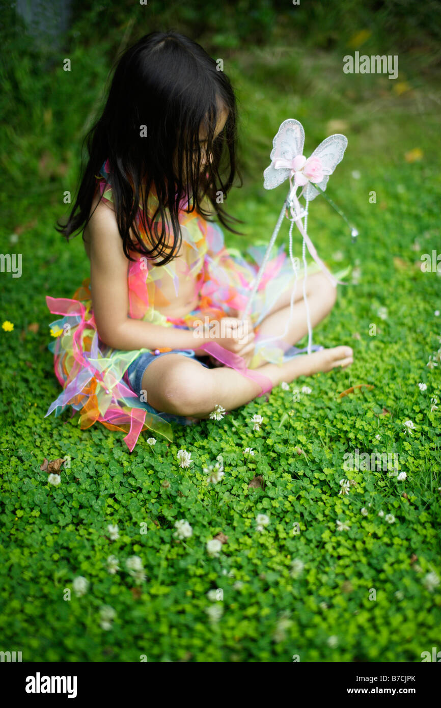Five year old girl in garden dressed up in her play clothes - Stock Image
