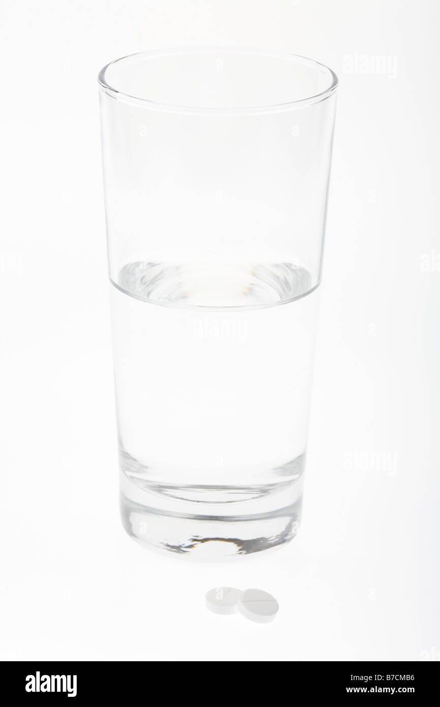 tall glass half full empty with water with two paracetamol tablets isolated on white background - Stock Image