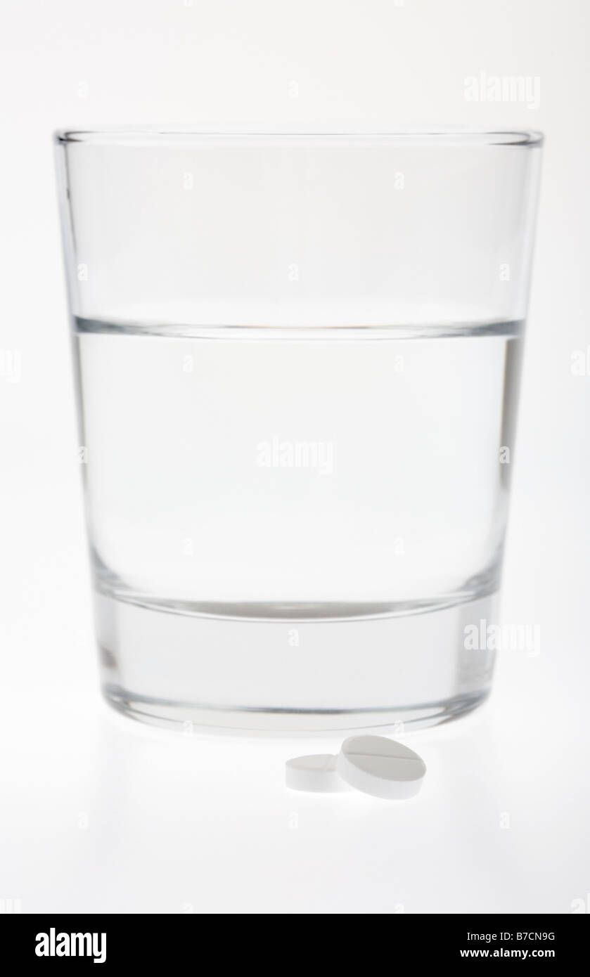 glass half full empty with water with two paracetamol tablets isolated on white background - Stock Image