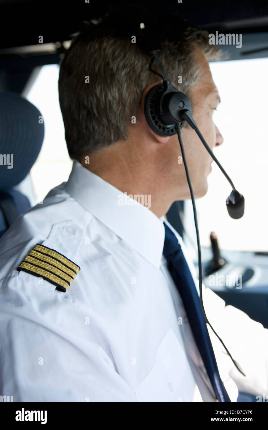 A pilot in the cockpit of a commercial plane - Stock Image