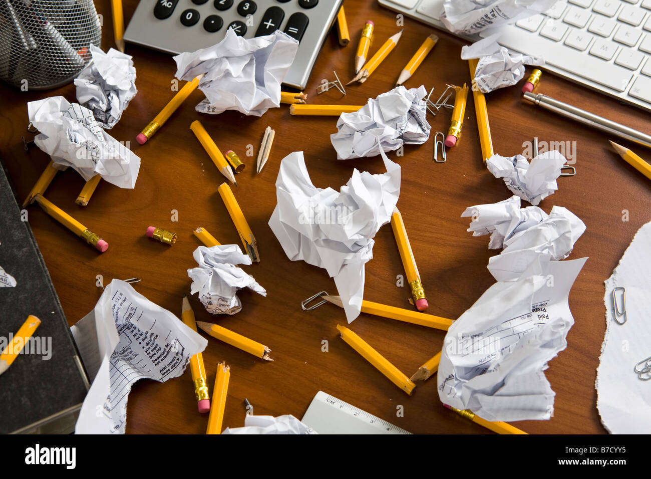 An office desk cluttered with pencils and crumpled paper - Stock Image