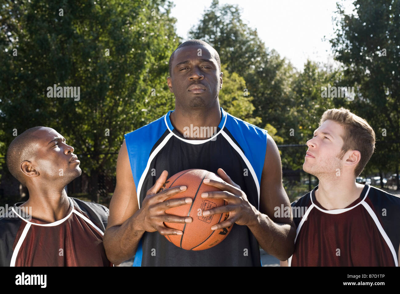 Three basketball players, in a row - Stock Image