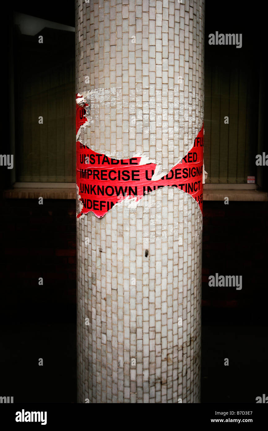 A torn typographical poster stuck to a pillar in east London. - Stock Image