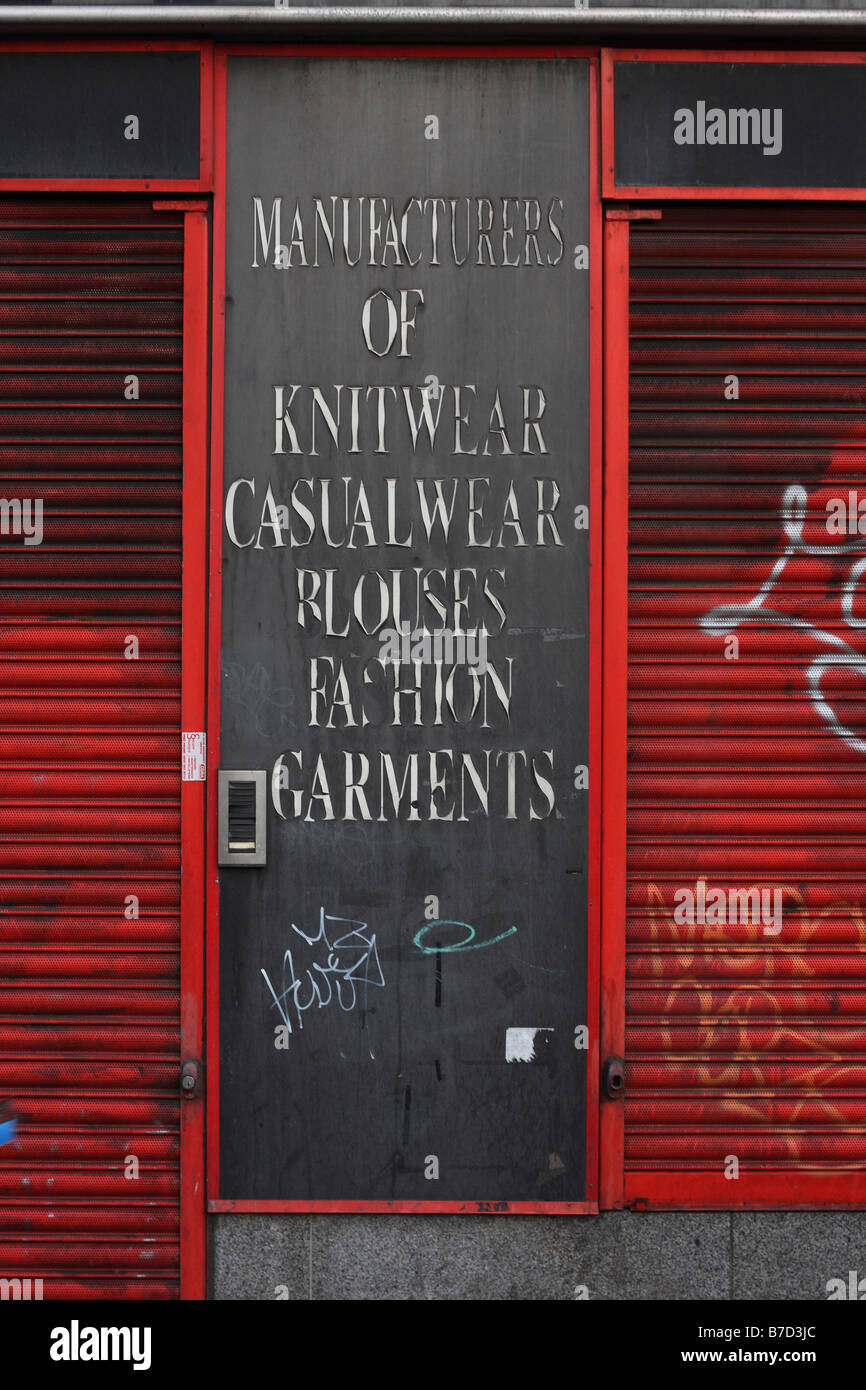 An old shop front sign advertising the fact that it is a manufacturer of knitwear, casualwear, blouses and fashion - Stock Image