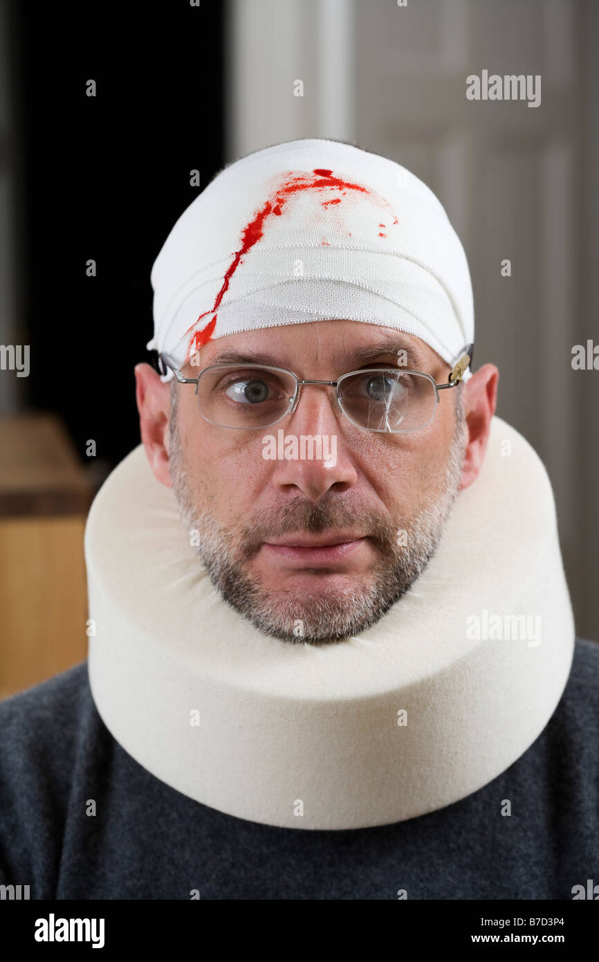 A man wearing cracked glasses, a bloody bandage on his head and a neck brace Stock Photo