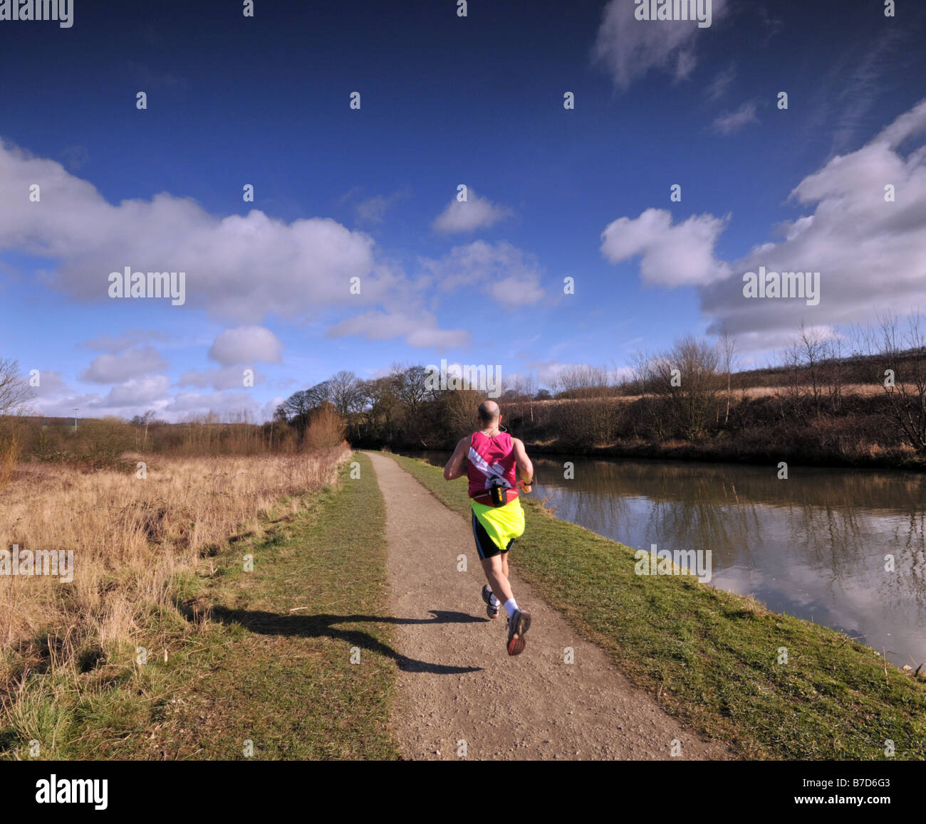 Jogger running along the towpath at Chesterfield Canal Derbyshire England UK - Stock Image