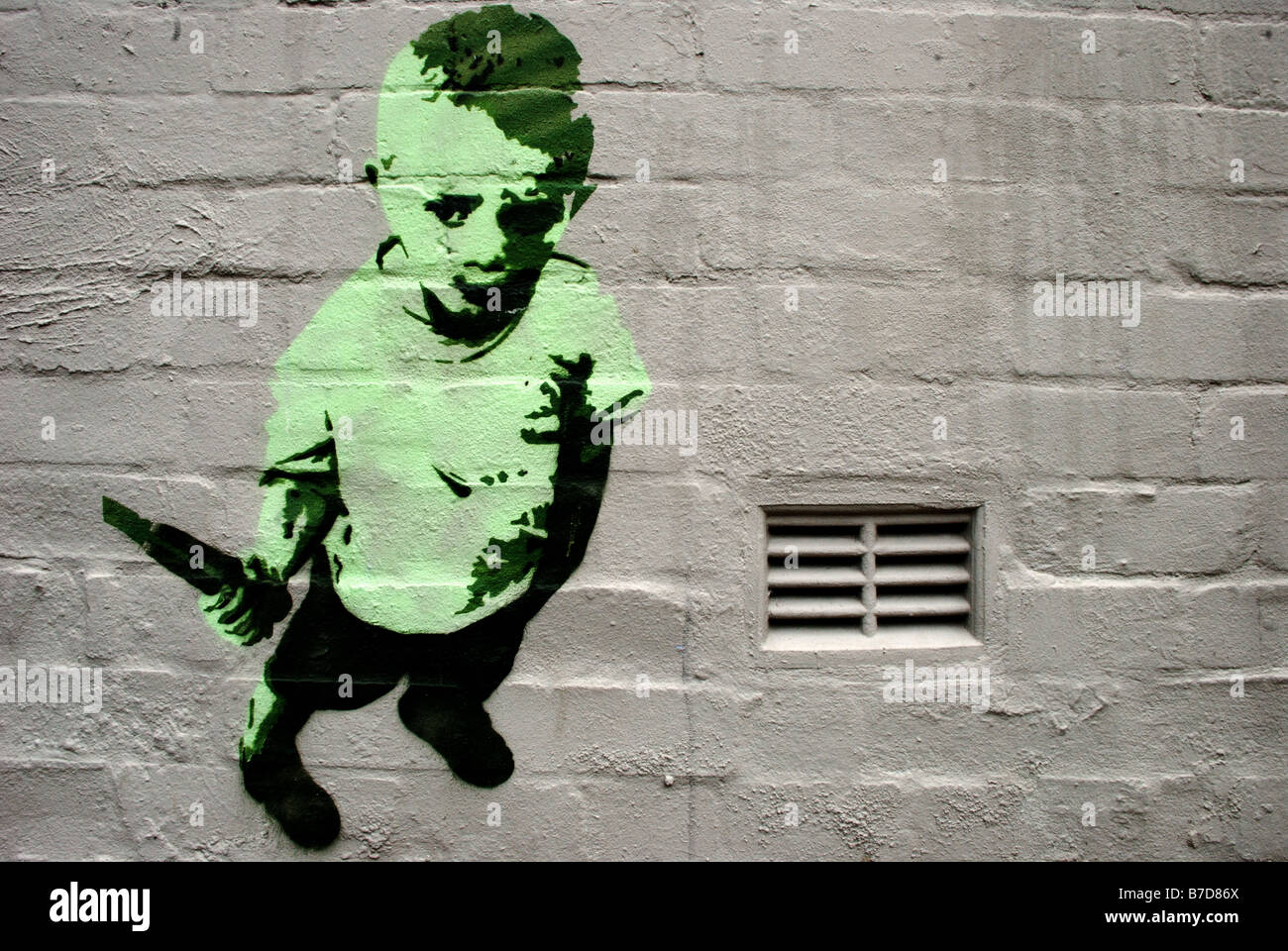 Stencil graffiti of a boy holding a knife placed near an air vent on a white washed terrace house wall - Stock Image