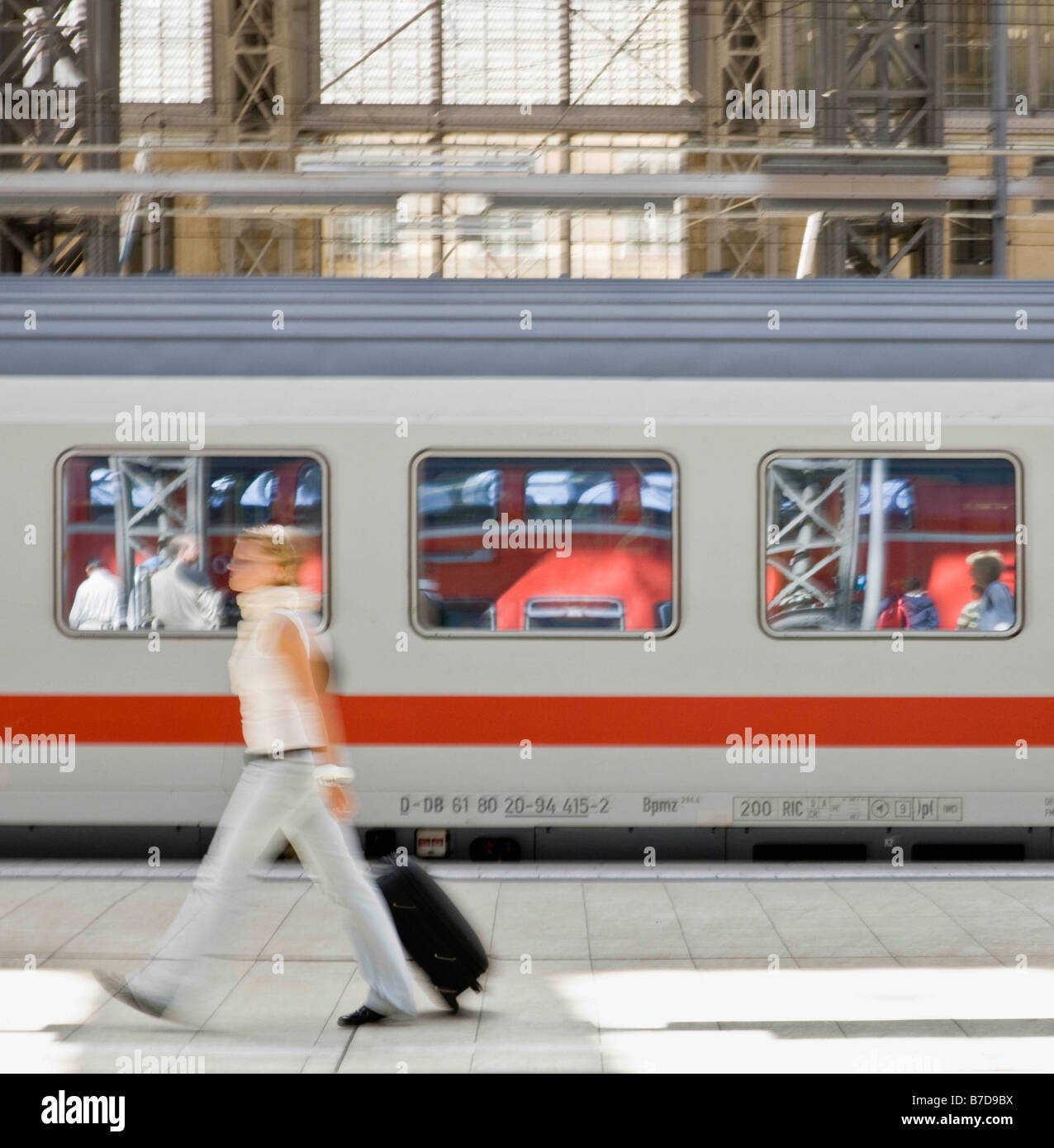Blur of woman walking past train - Stock Image