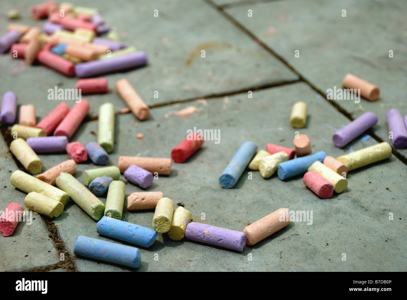 Pieces of coloured chalk scattered on a paved ground, in shallow focus. - Stock Image
