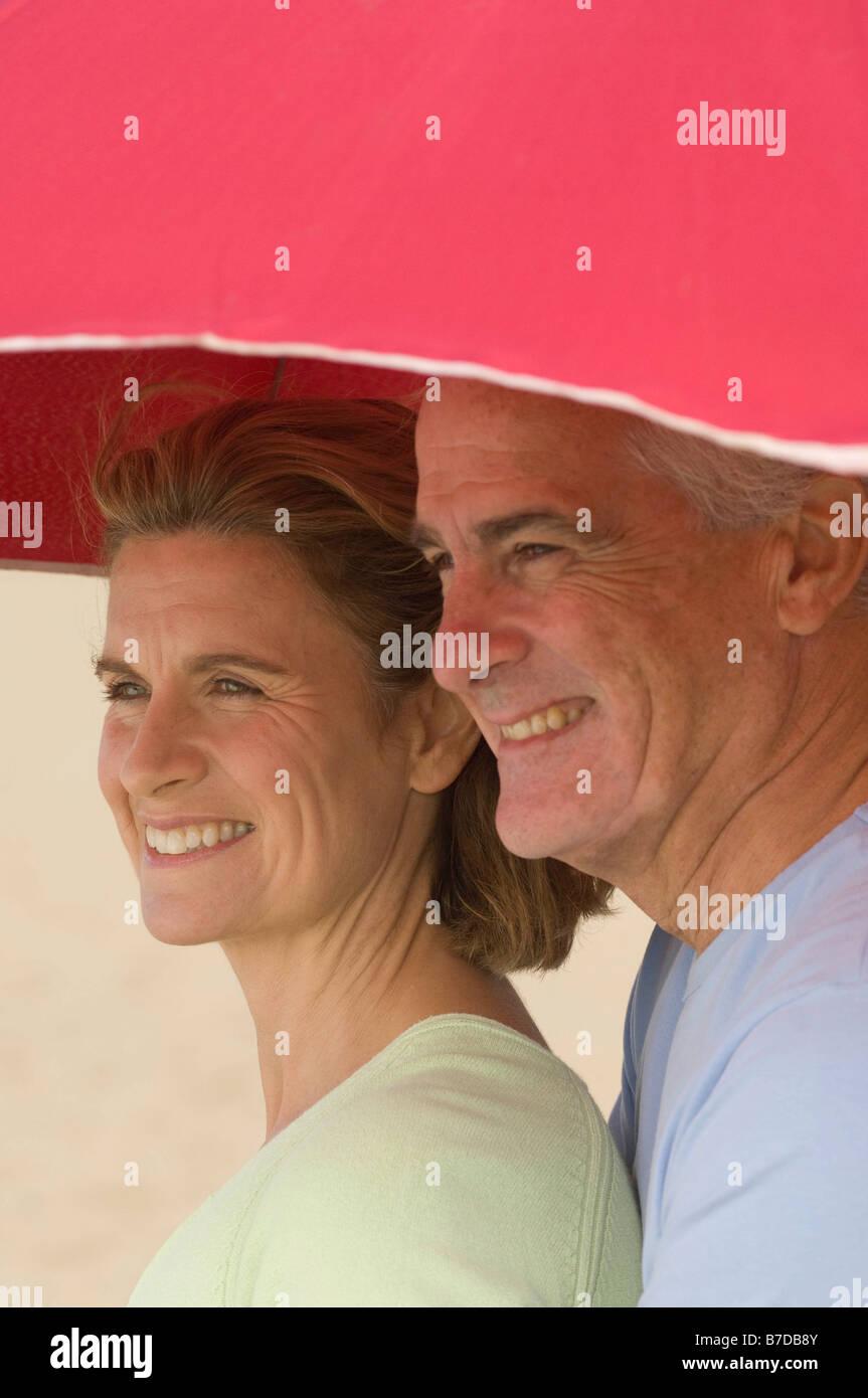 Couple sheltering under beach parasol - Stock Image
